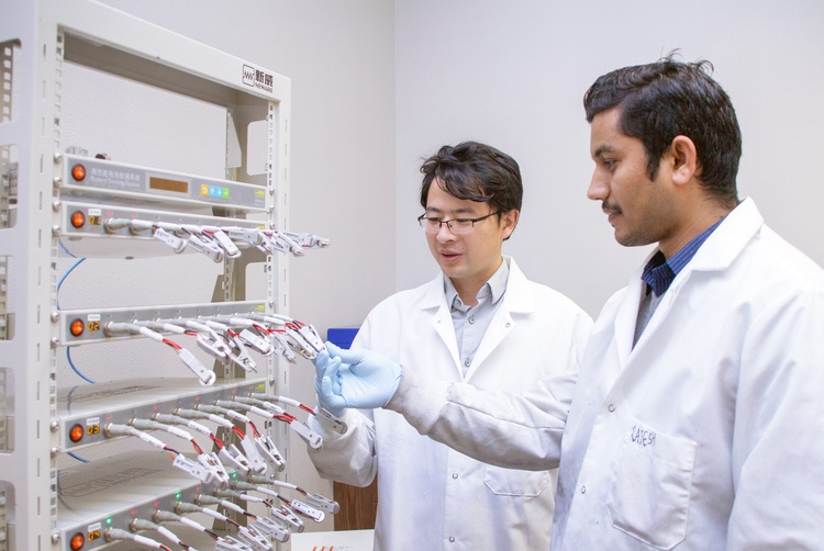 Assistant Professor Yue Zhou, left, and doctoral student Rajesh Pathak of the South Dakota State University Department of Electrical Engineering and Computer Science test cycle life and other electric performances of lithium-ion batteries. Through a grant from the South Dakota Board of Regents, Zhou and his team will develop a new solid polymer material designed to improve the performance of lithium-ion batteries. SDSU photo.